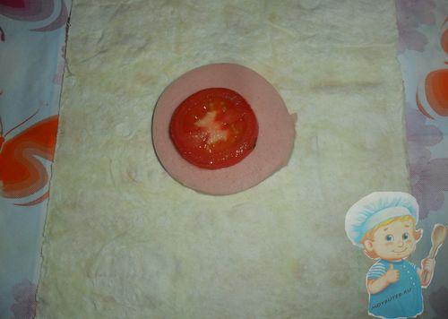 Выкладываем на лаваш колбаску и потом помидор
